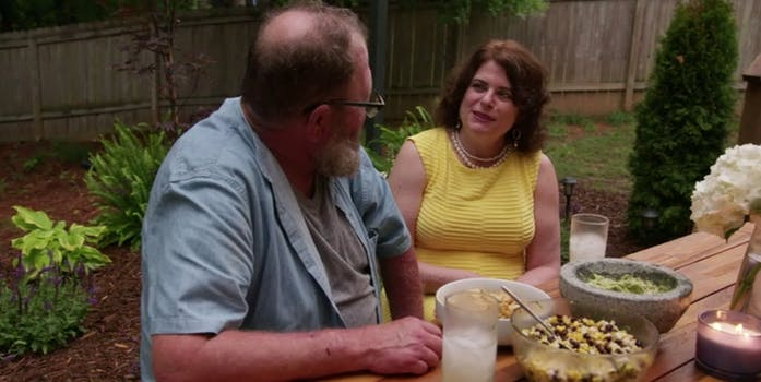 Tom and Abby sit at a picnic table, smiling at each other