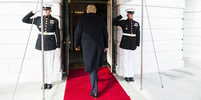 Donald Trump flanked by US Marines as he enters the White House