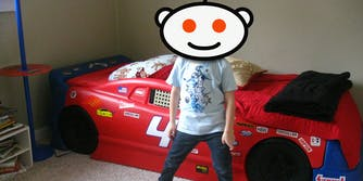 Child with Reddit Snoo head stands in front of race car bed