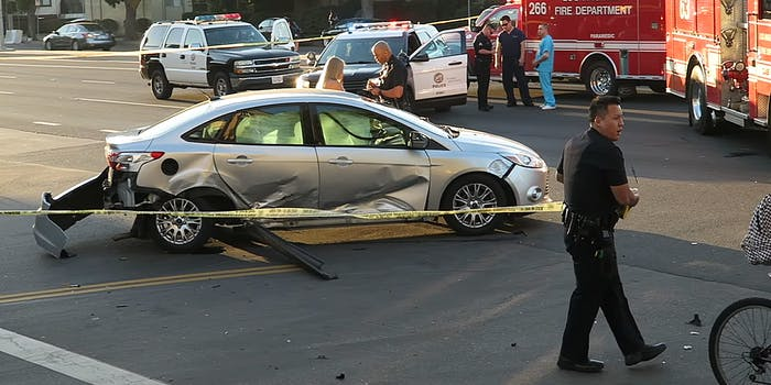 Police officer deploying yellow tape around accident scene
