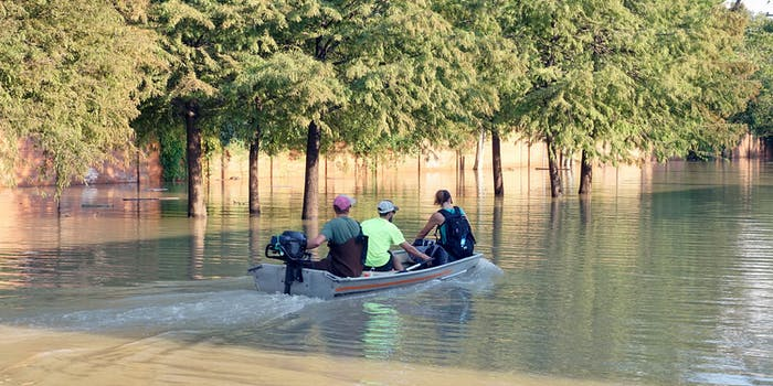 Three people in a boat during Hurricane Harvey.