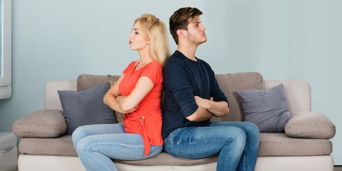 A couple sitting on a couch facing away from each other.