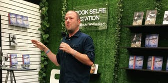 Jay Asher speaks into a microphone