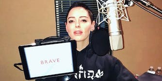 Rose McGowan holds up an iPad displaying the title of her book, 'Brave'