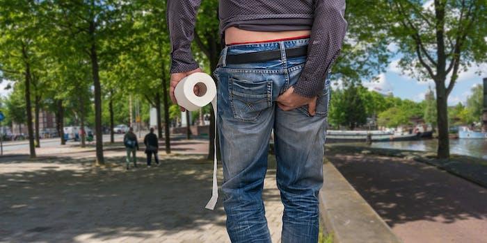 Man holding toilet paper on street
