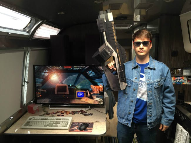 Stephen Raney, lead programmer on Strafe, posing with a low poly machine gun.