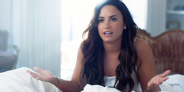 Demi Lovato sitting on bed, talking