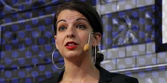 Anita Sarkeesian in front of Drip logo pattern